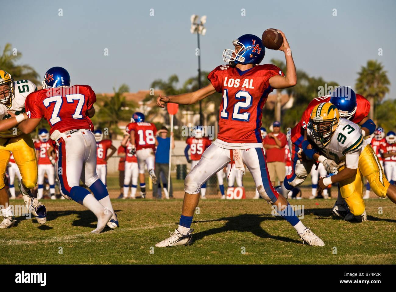 Un jugador lanzando el balón en un partido de fútbol americano con futbolistas corriendo alrededor, Huntington Beach, California, EE.UU. Foto de stock