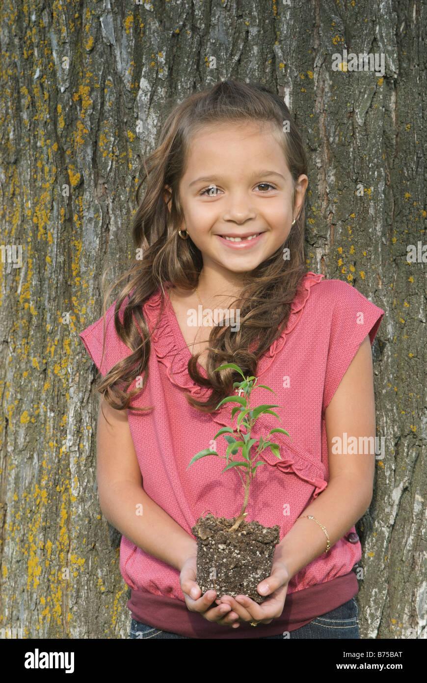 Los siete años de edad, niña celebración seedling junto a árbol, Winnipeg, Canadá Foto de stock