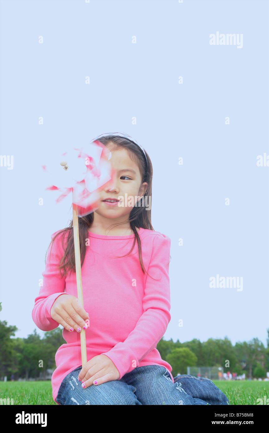 Niña de cinco años en el parque con rueda dentada, Winnipeg, Canadá Foto de stock