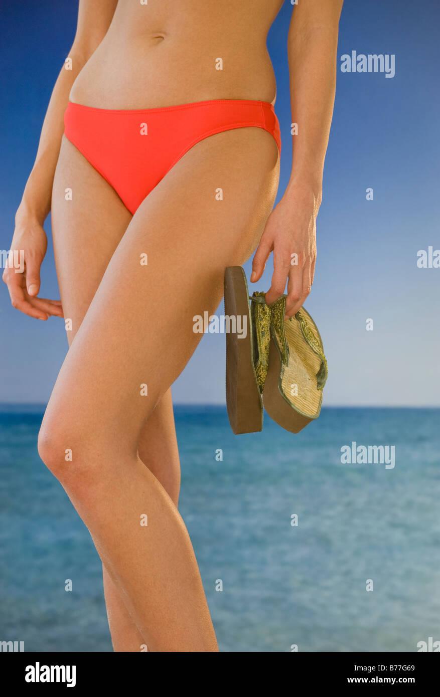 La mitad del torso de mujer bikini sosteniendo los flip-flops en la playa Imagen De Stock