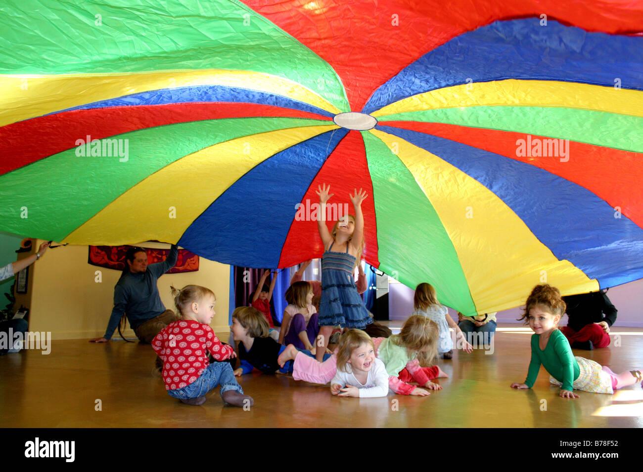 Libere a los niños jugando bajo uplifted coloridos paracaídas en California play group Imagen De Stock