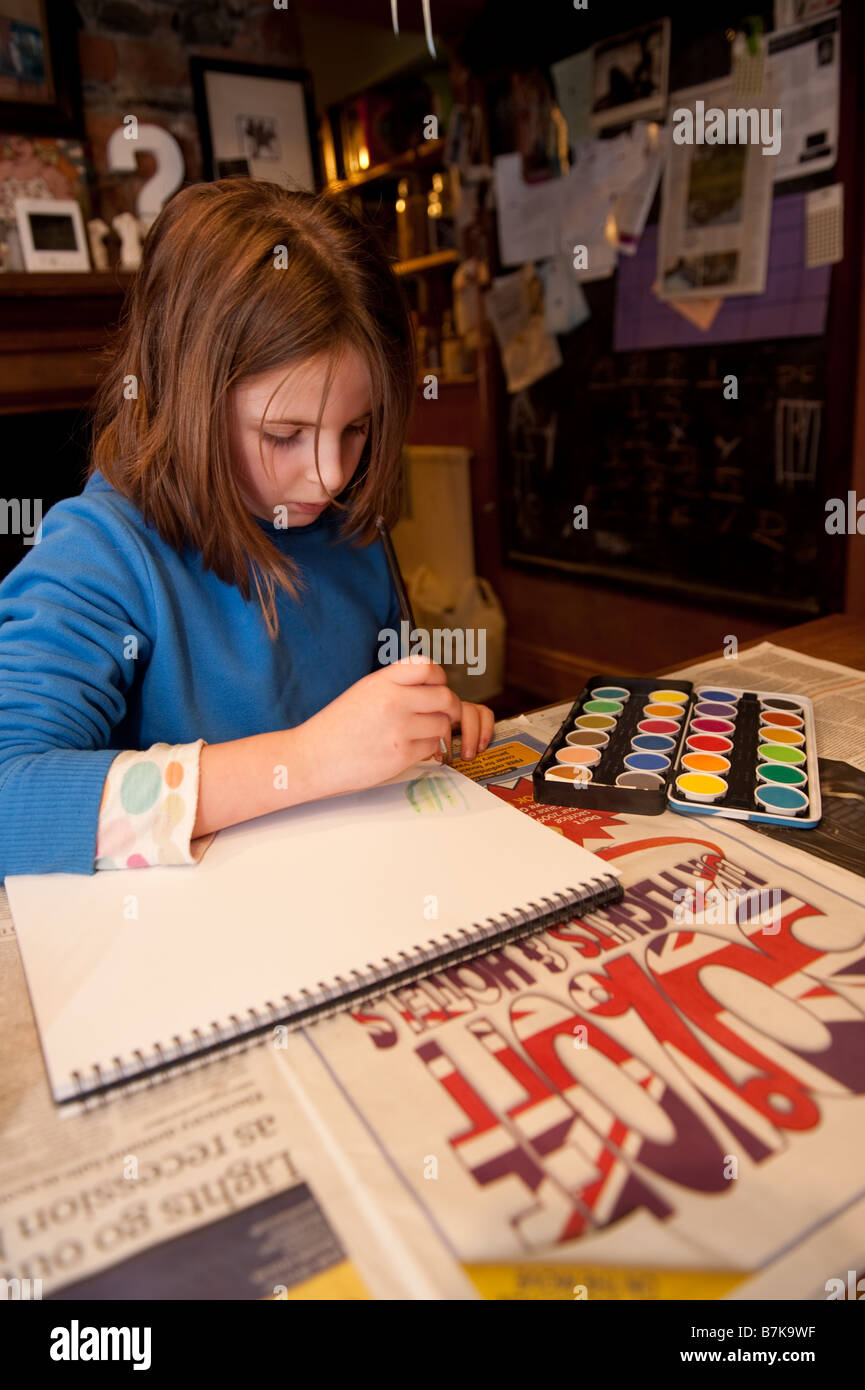 9 10 11 años de edad, niña pintar un cuadro en casa sobre la mesa de la cocina, REINO UNIDO Imagen De Stock