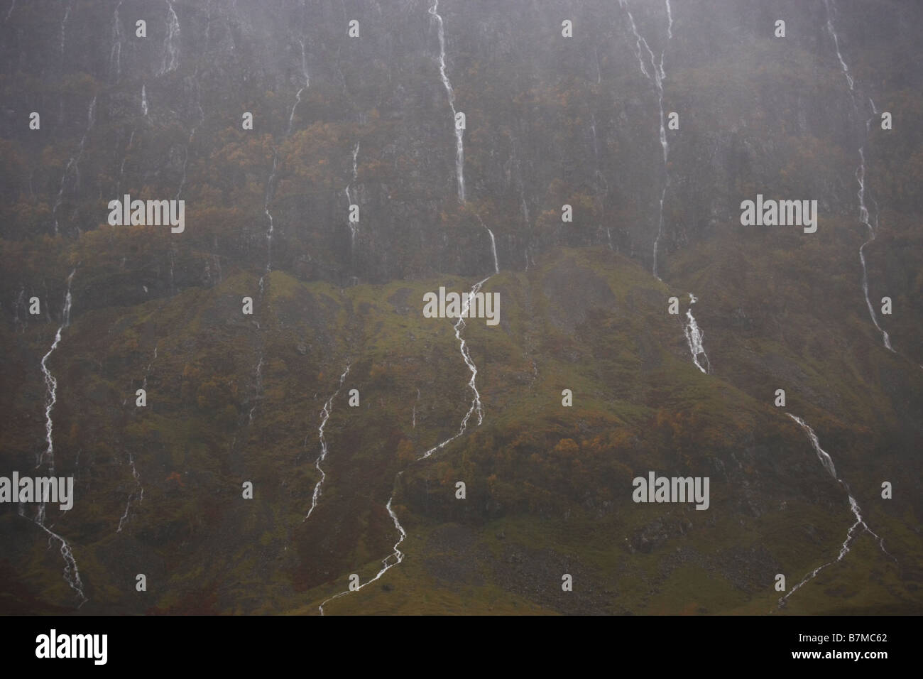El lado de la montaña y arroyos durante el mal tiempo y la lluvia torrencial de Glen Coe Highlands de Escocia Imagen De Stock
