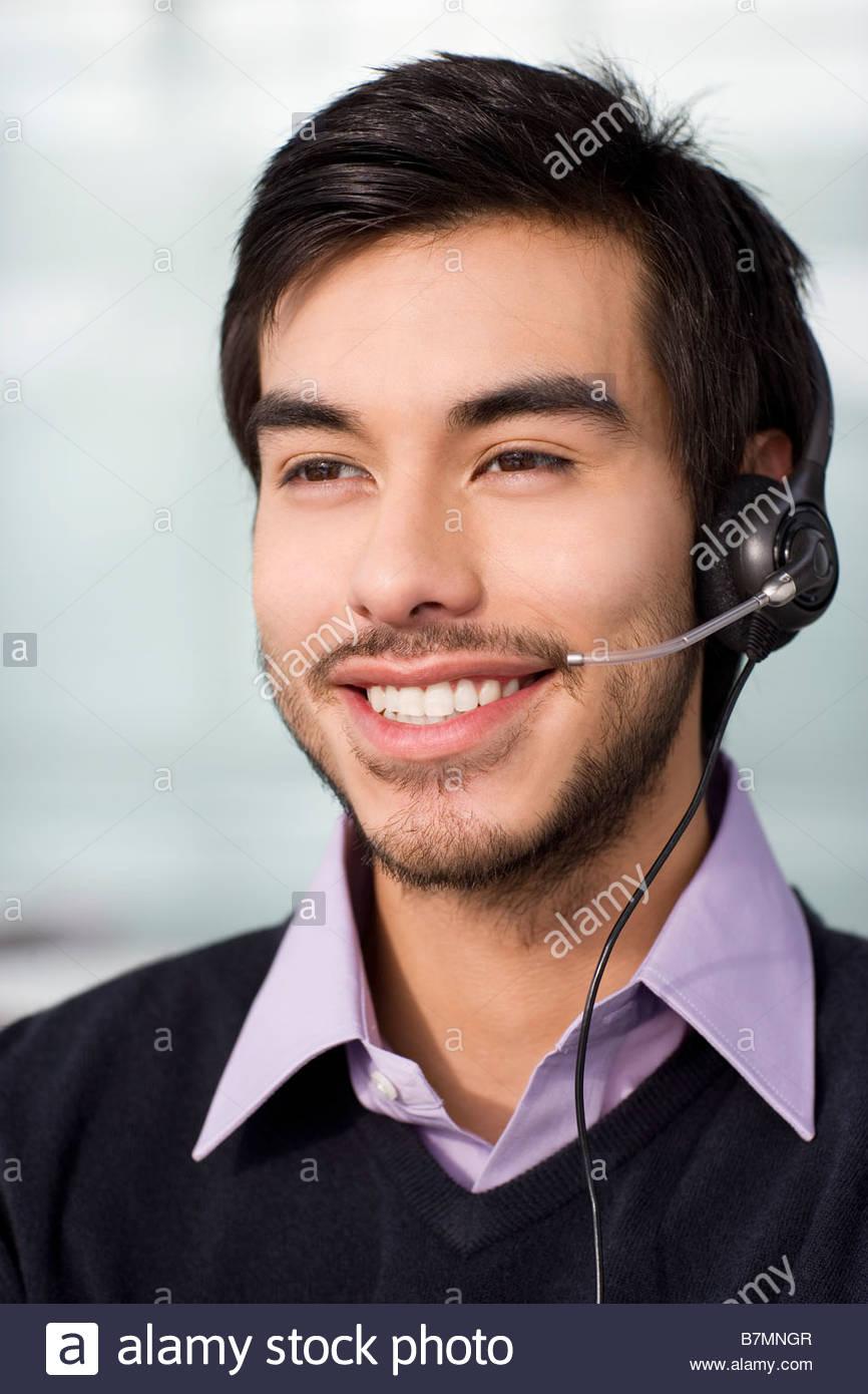 Una morenaza luciendo un macho televentas auriculares Imagen De Stock