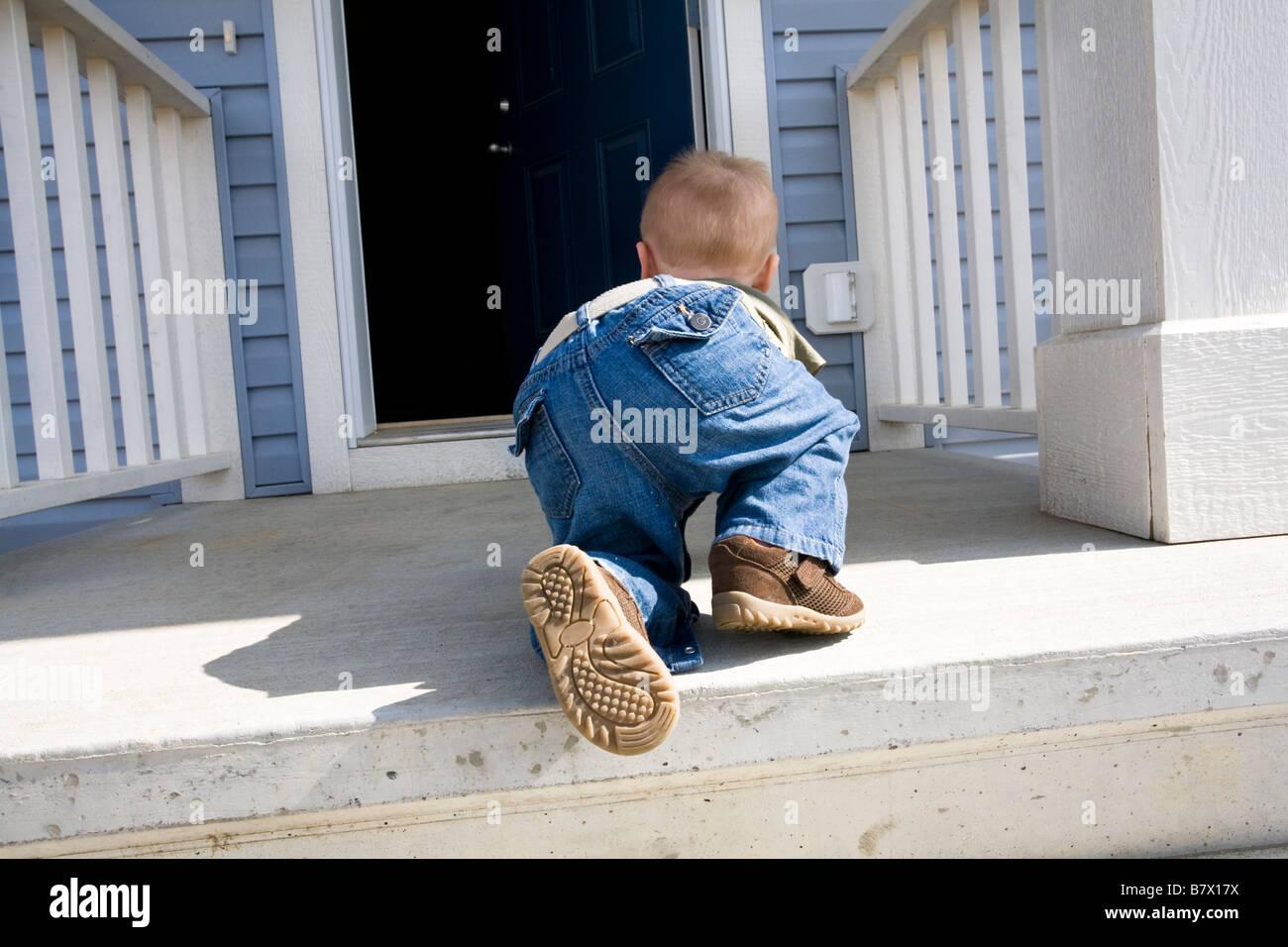 Niño arrastrándose hacia la puerta abierta Foto de stock
