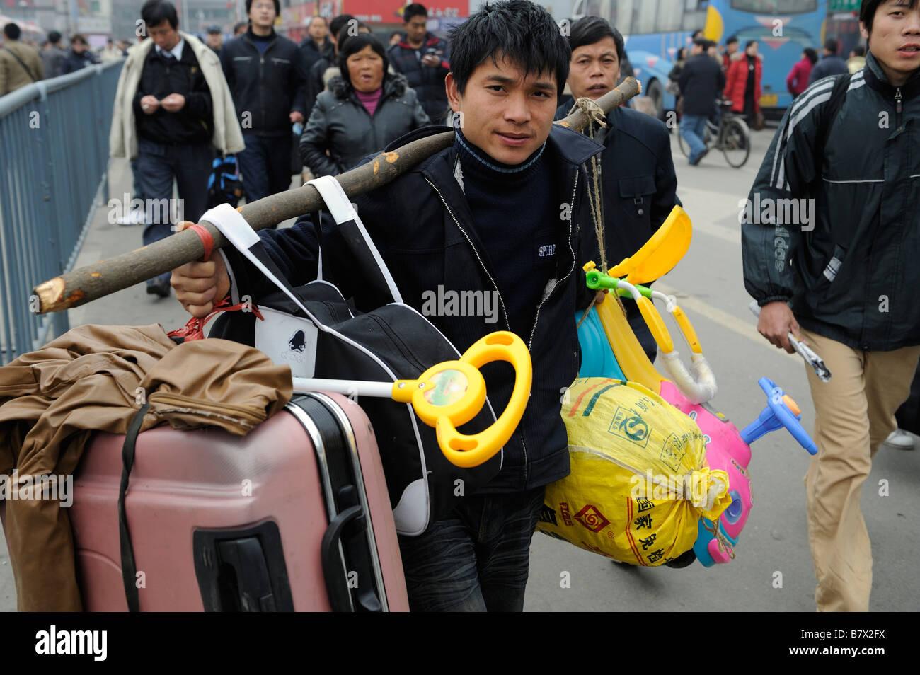 Los trabajadores migrantes transportar su equipaje al salir de la estación de trenes de Nanchang, Jiangxi, Imagen De Stock