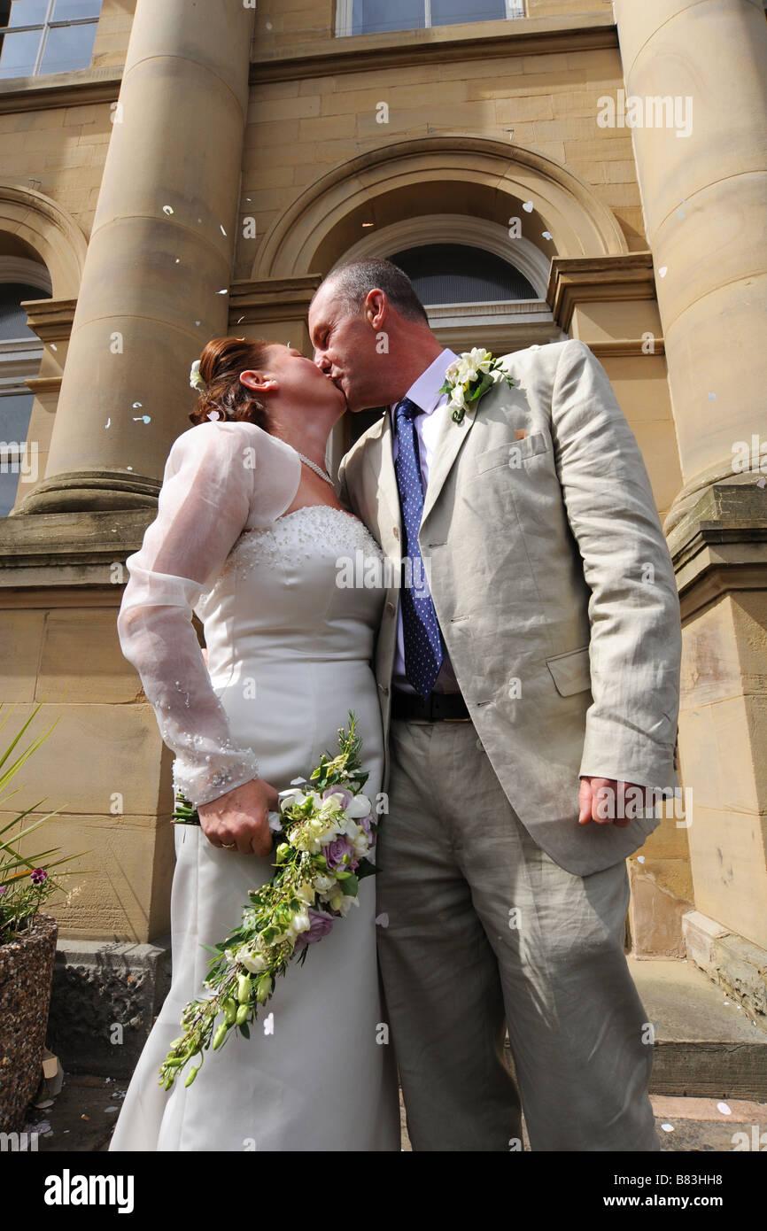 Recién casados besándose fuera de una oficina del registro civil, North Yorkshire modelo liberado Imagen De Stock