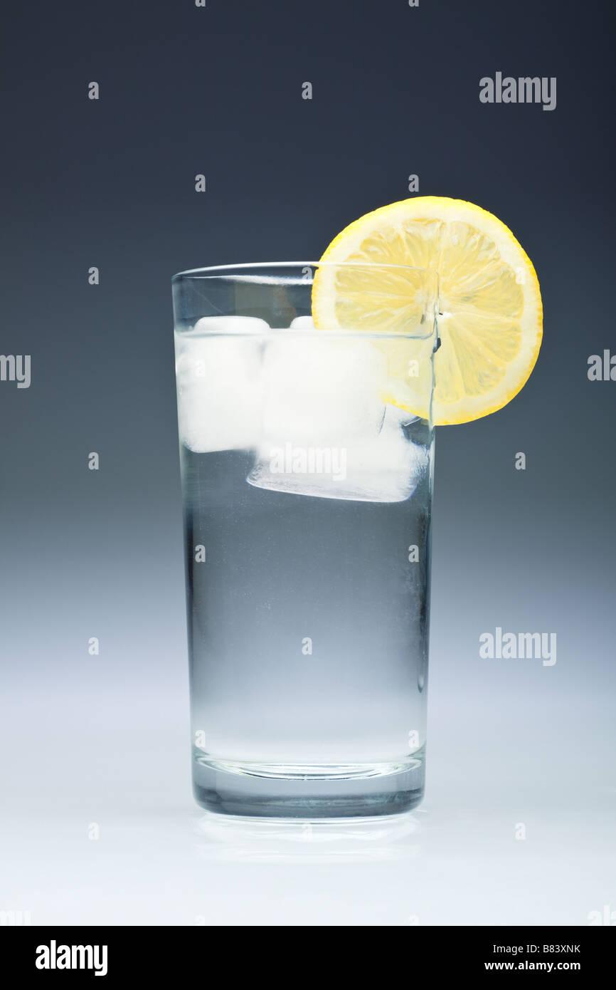 Vaso de agua con cubitos de hielo y una rodaja de limón cerrar studio Imagen De Stock