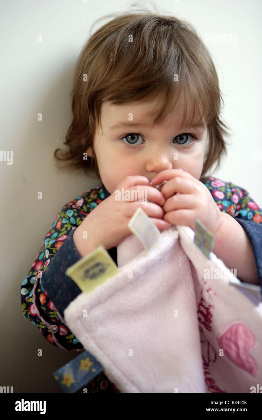 Un bebé de un año de edad chica masticando una manta de confort Imagen De Stock