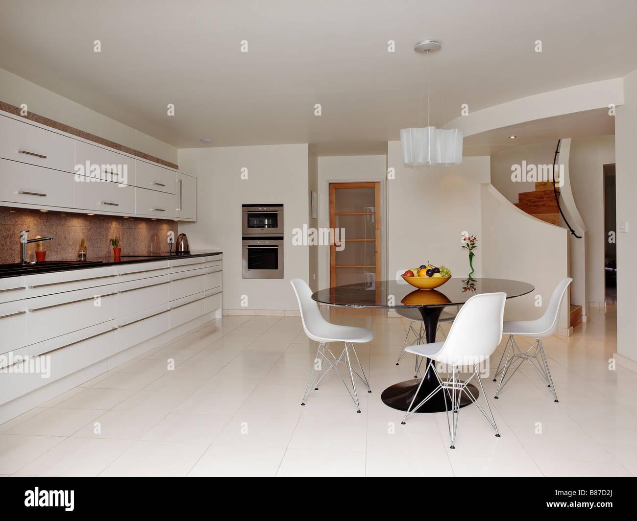 Blanco contemporáneo cocina con mesa redonda y frutero y escalera de ...