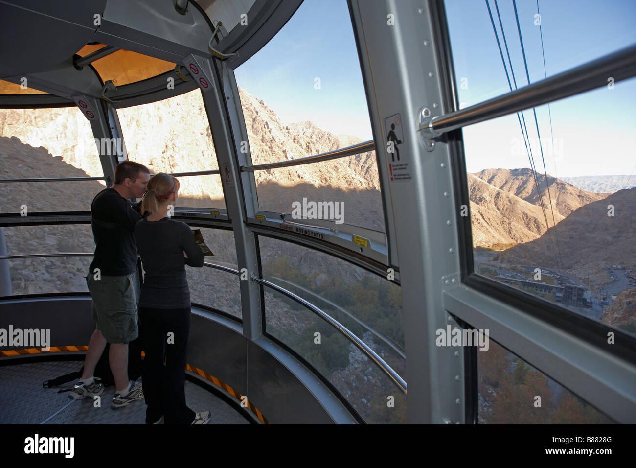 Turistas mirando al paisaje natural de los alrededores mientras viajan en Palm Springs Aerial Tramway. Palm Springs, Foto de stock
