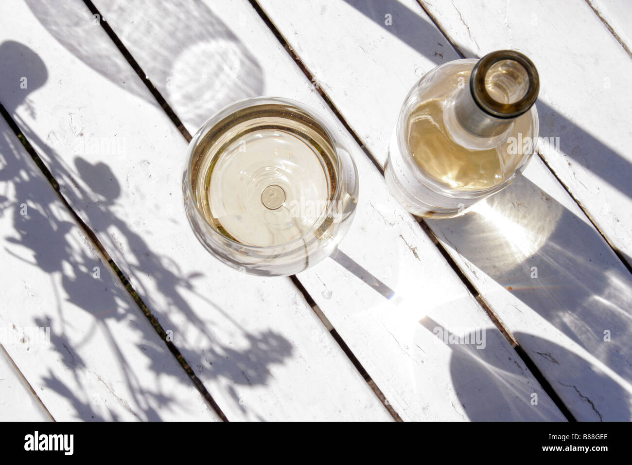 Una botella de vino blanco y un vaso colocado fuera sobre una tabla de madera blanca. Imagen De Stock