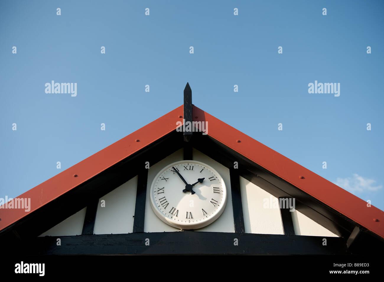 Reloj en pabellón de deportes exterior situado a cinco minutos a dos 1 55pm, el azul claro del cielo Imagen De Stock