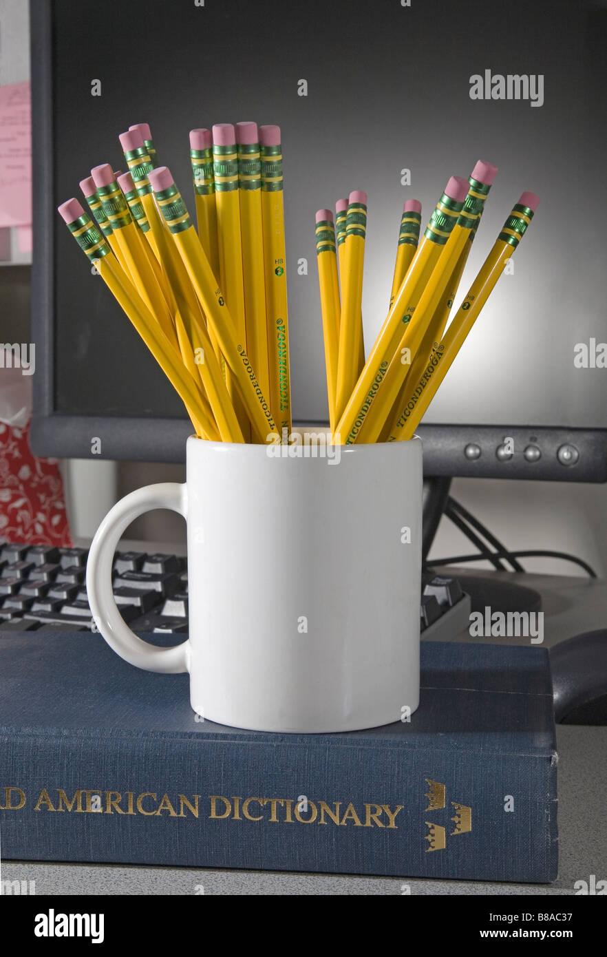 Un vaso o taza de Ticonderoga número 2 derivaciones o lápices de grafito y borradores en frente de una Imagen De Stock