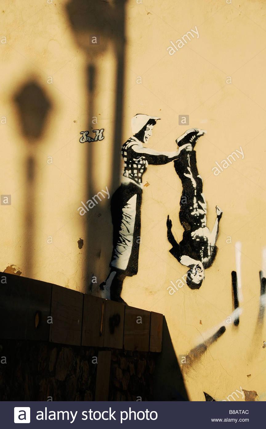 Grafito representando a una mujer a punto de lanzar un joven fuera del borde de una pared Imagen De Stock