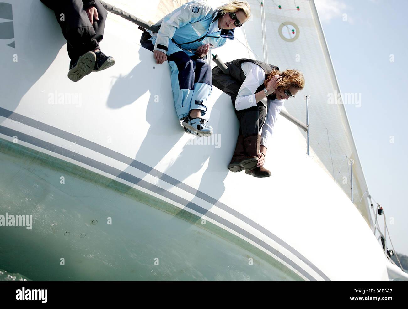 3 adultos, 2 mujeres y 1 hombre inclinado sobre la banda de estribor de un velero. La imagen en color en formato Imagen De Stock