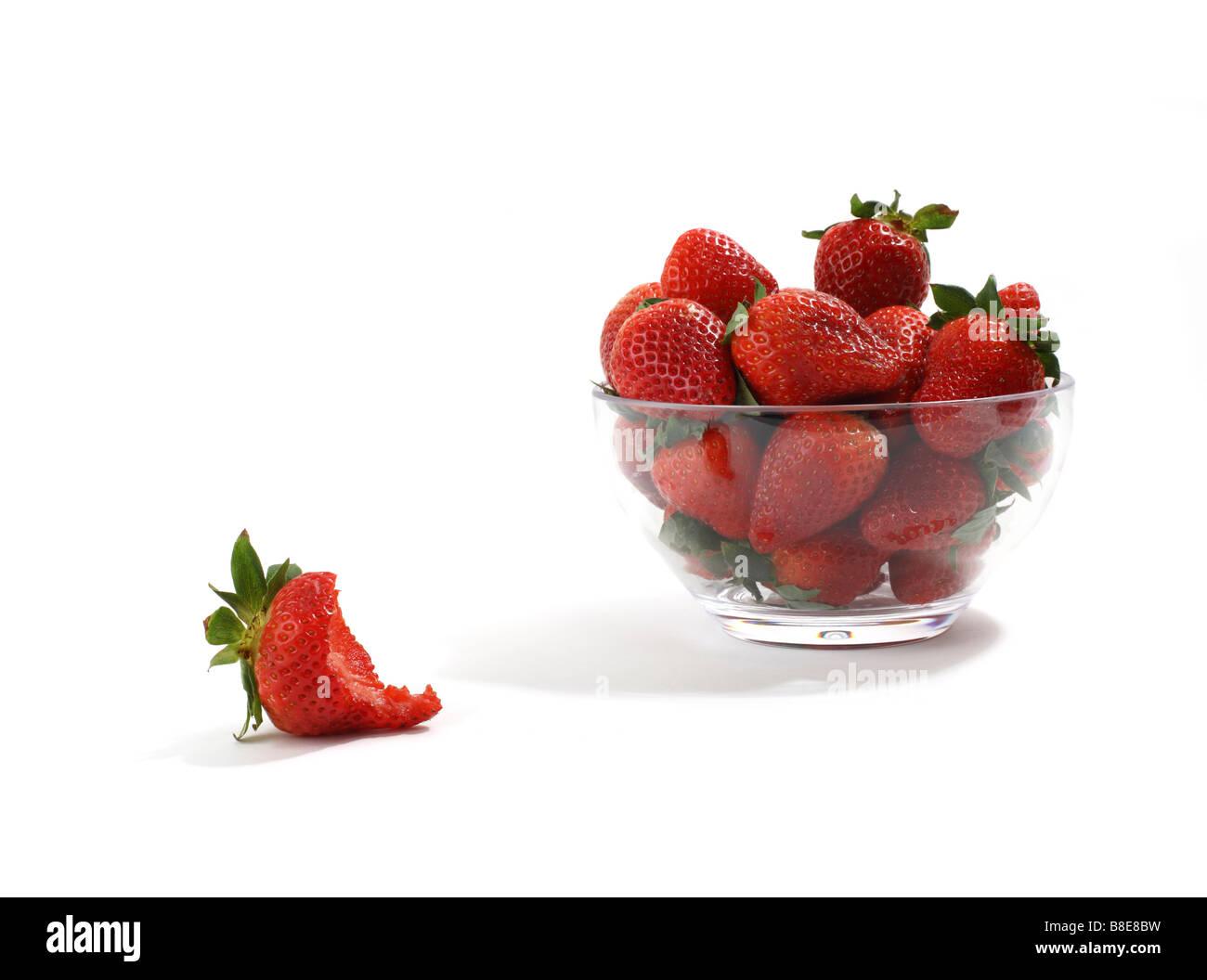 Tazón de fresas rojas con uno come en primer plano Imagen De Stock