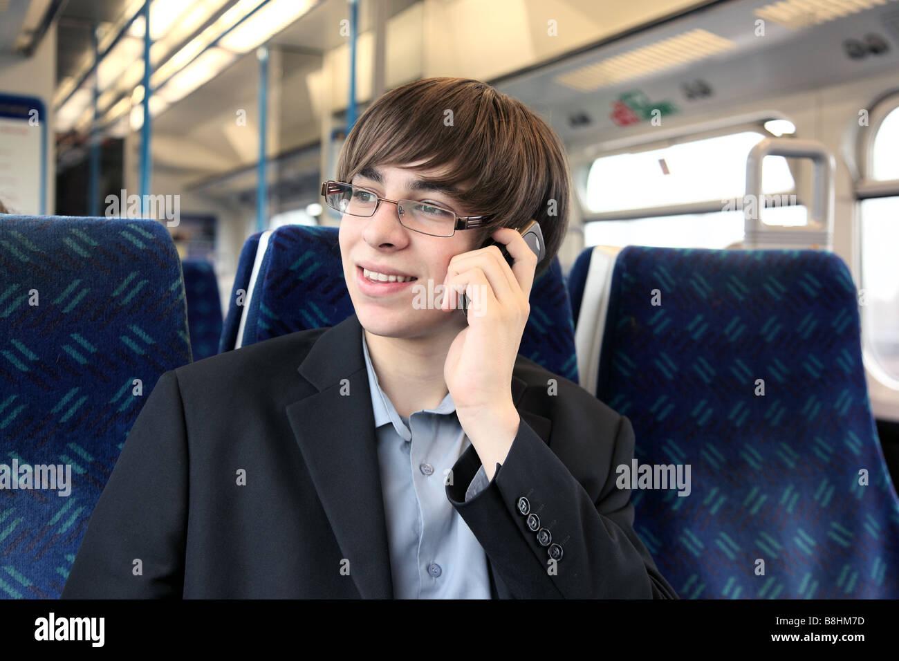 Un hombre joven con un teléfono móvil o celular en un tren Imagen De Stock