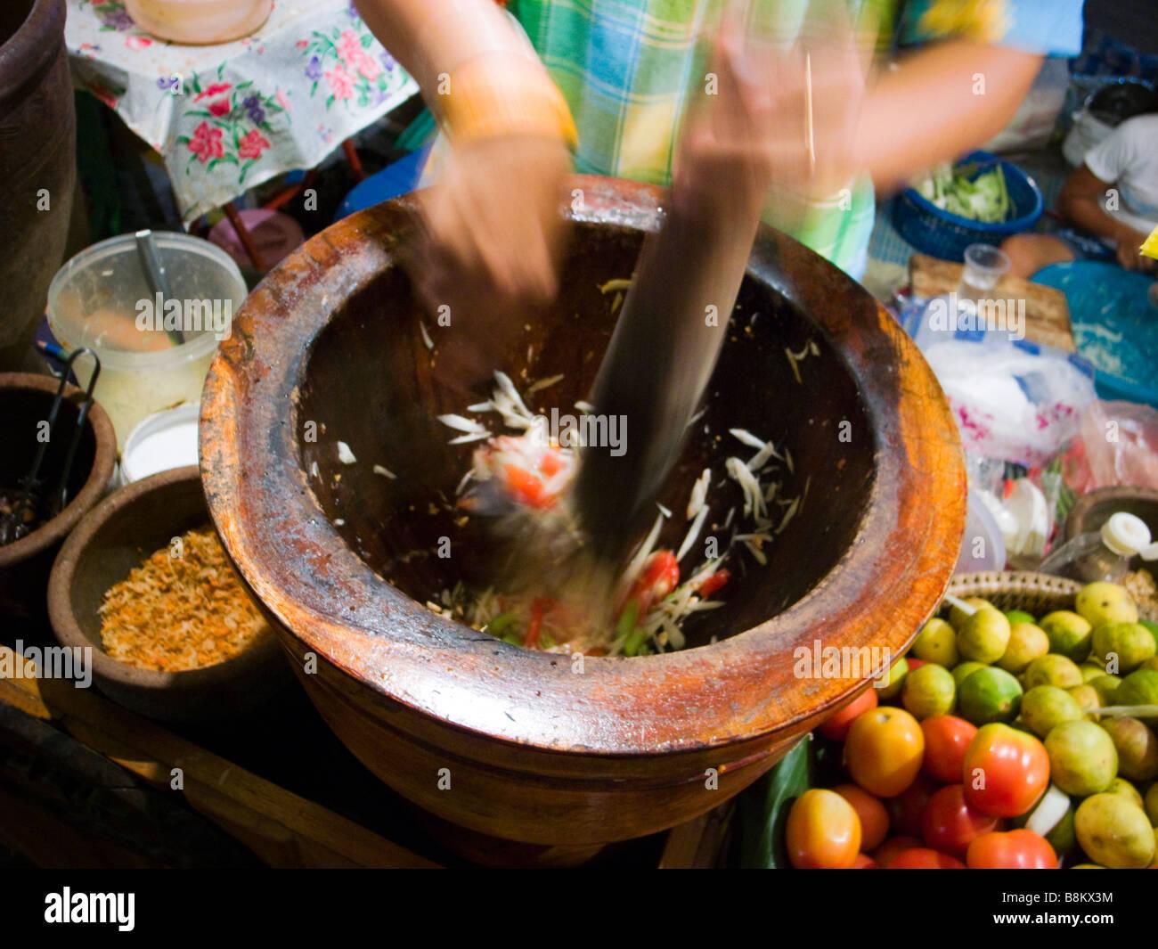 Detalle del vendedor ambulante tailandés hacer ensalada de papaya picante en el mercado nocturno en Trang Tailandia Imagen De Stock