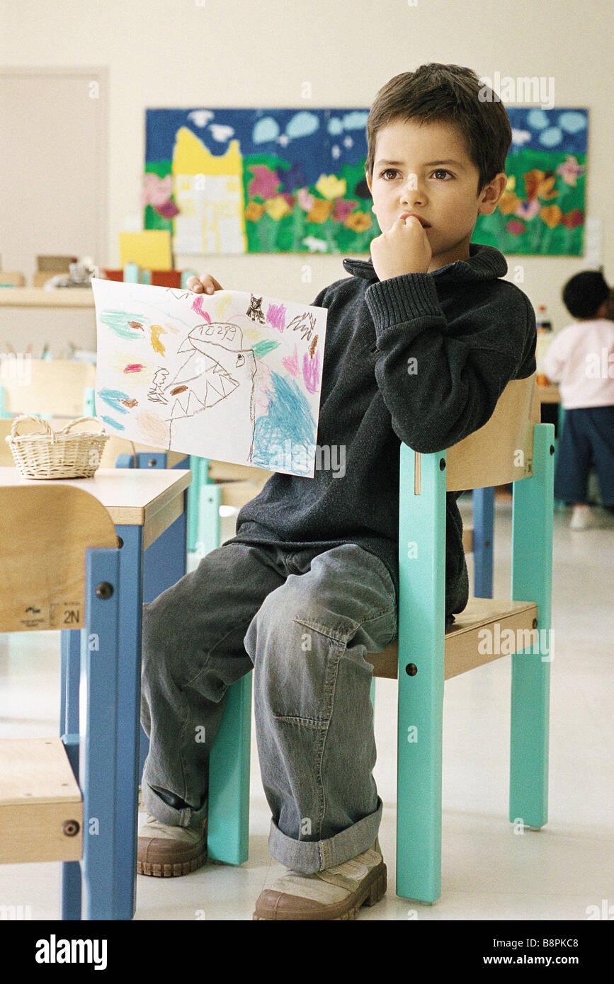 niño sentándose en la silla de clase
