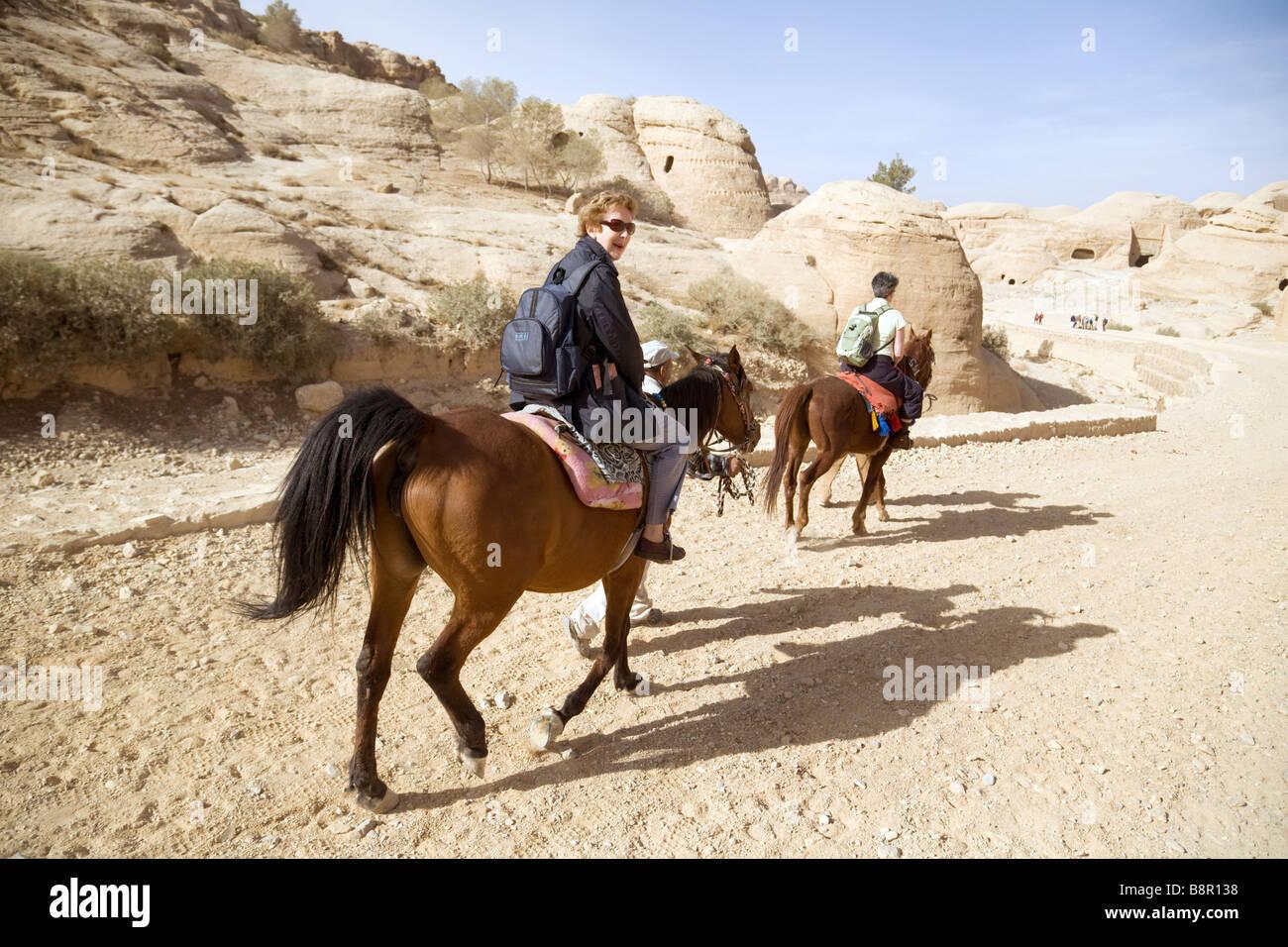Los turistas a caballo en Petra, Jordania, Oriente Medio Imagen De Stock