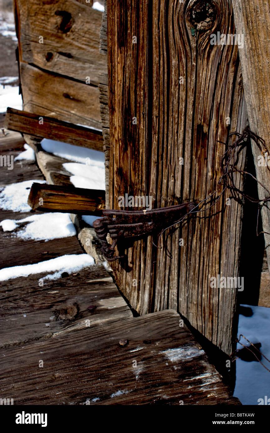 Rusty bisagra vieja y la nieve en un expulsor de ganado Foto de stock