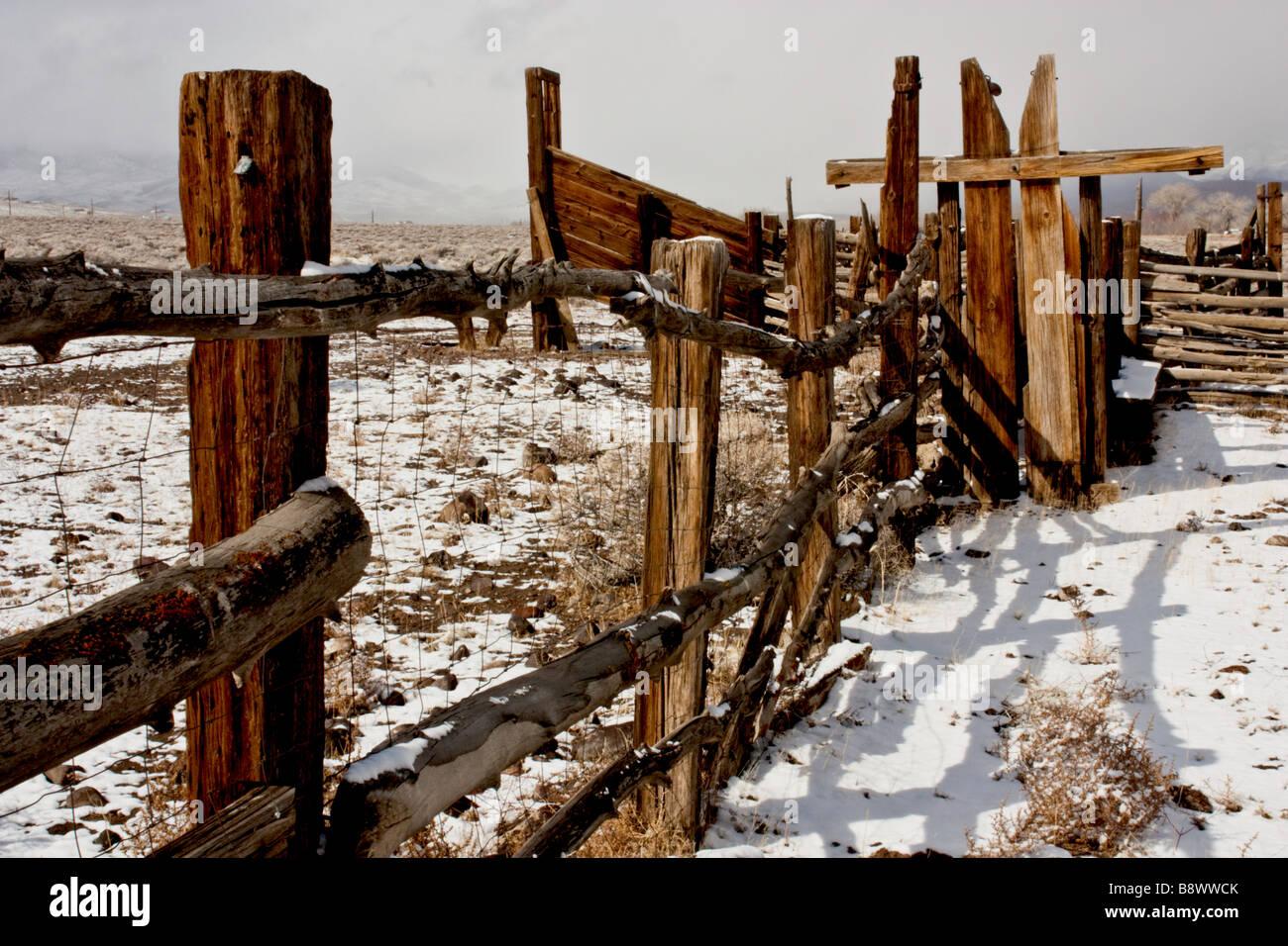 La nieve fresca y una valla de madera desgastada de un corral mientras una nevasca enfoques Foto de stock