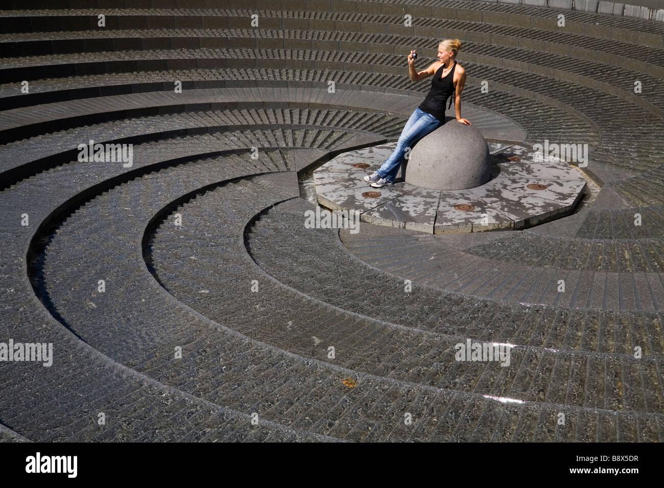 Turista fotografiando la espiral Fuente en Puerto Darling, Sydney, New South Wales, Australia Imagen De Stock