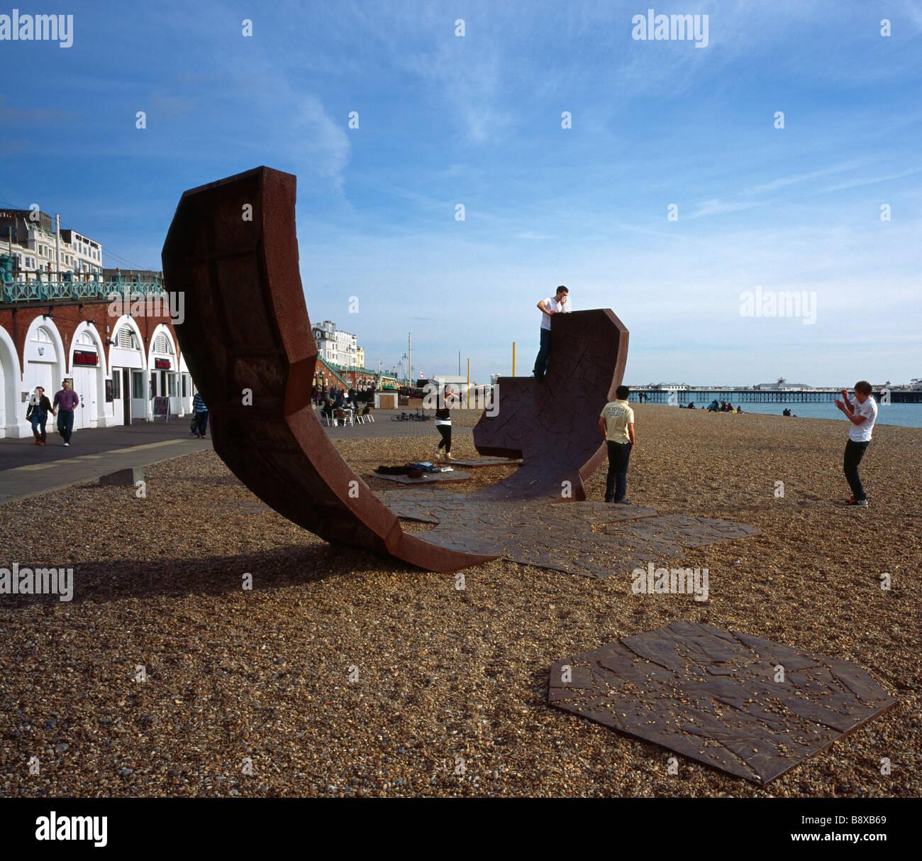 Adolescentes jugando en una escultura de arte moderno llamado pasacalles. La playa de Brighton, Sussex, Inglaterra, Reino Unido. Foto de stock