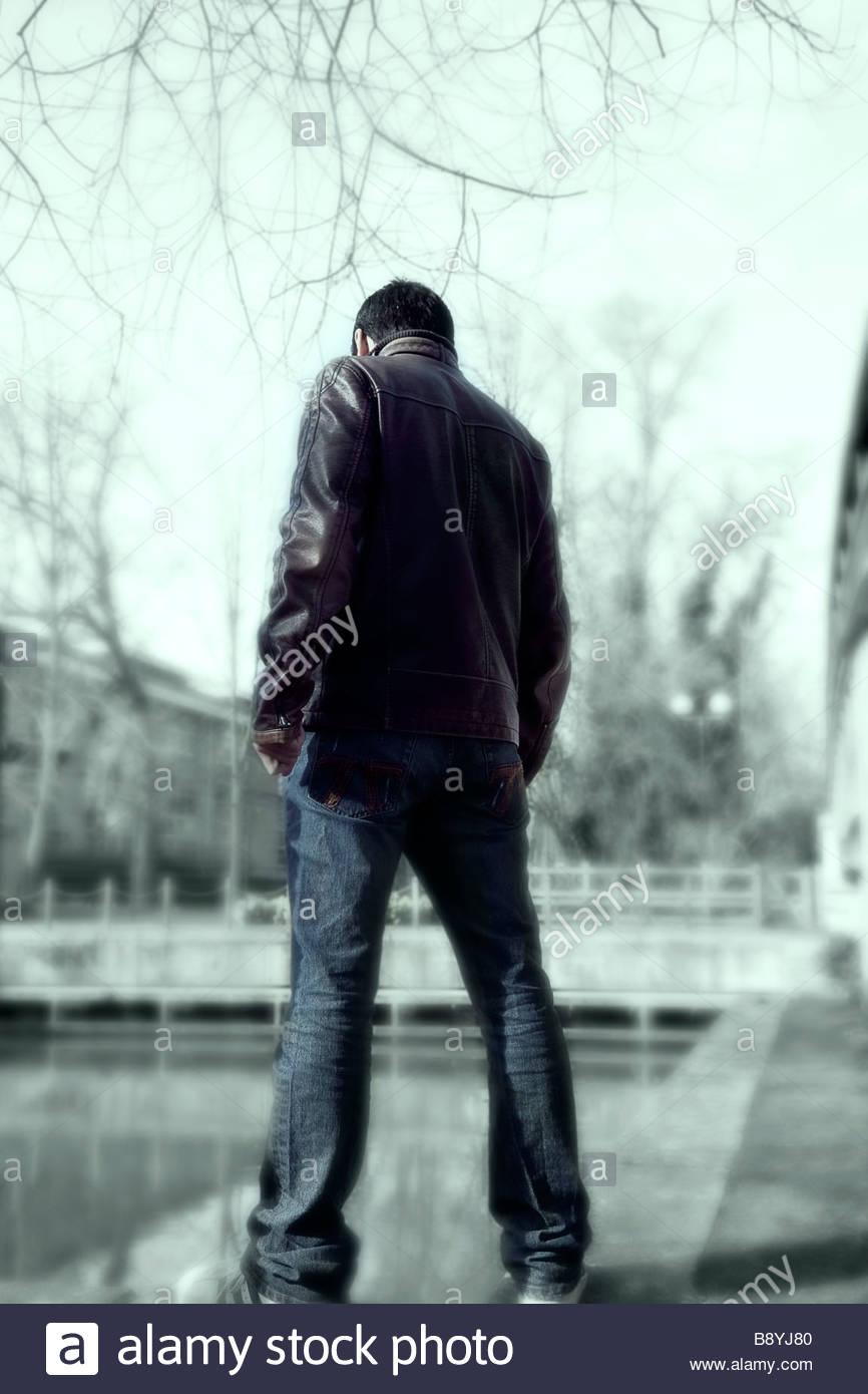 El hombre en la reflexión profunda mirando al lago Imagen De Stock