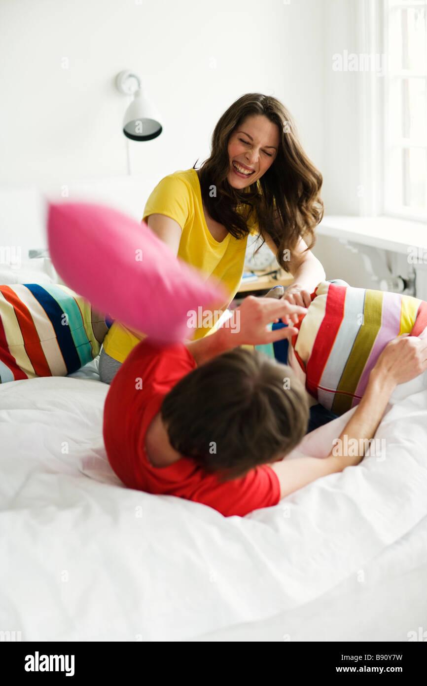 Una pareja joven con una almohada-lucha. Imagen De Stock