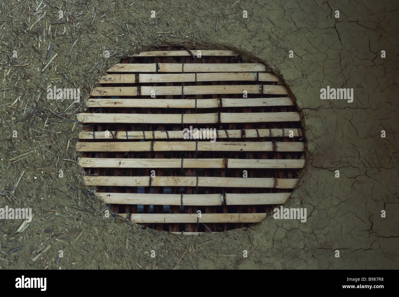 Ventana en la pared de adobe, cubierta por cañas de bambú Imagen De Stock