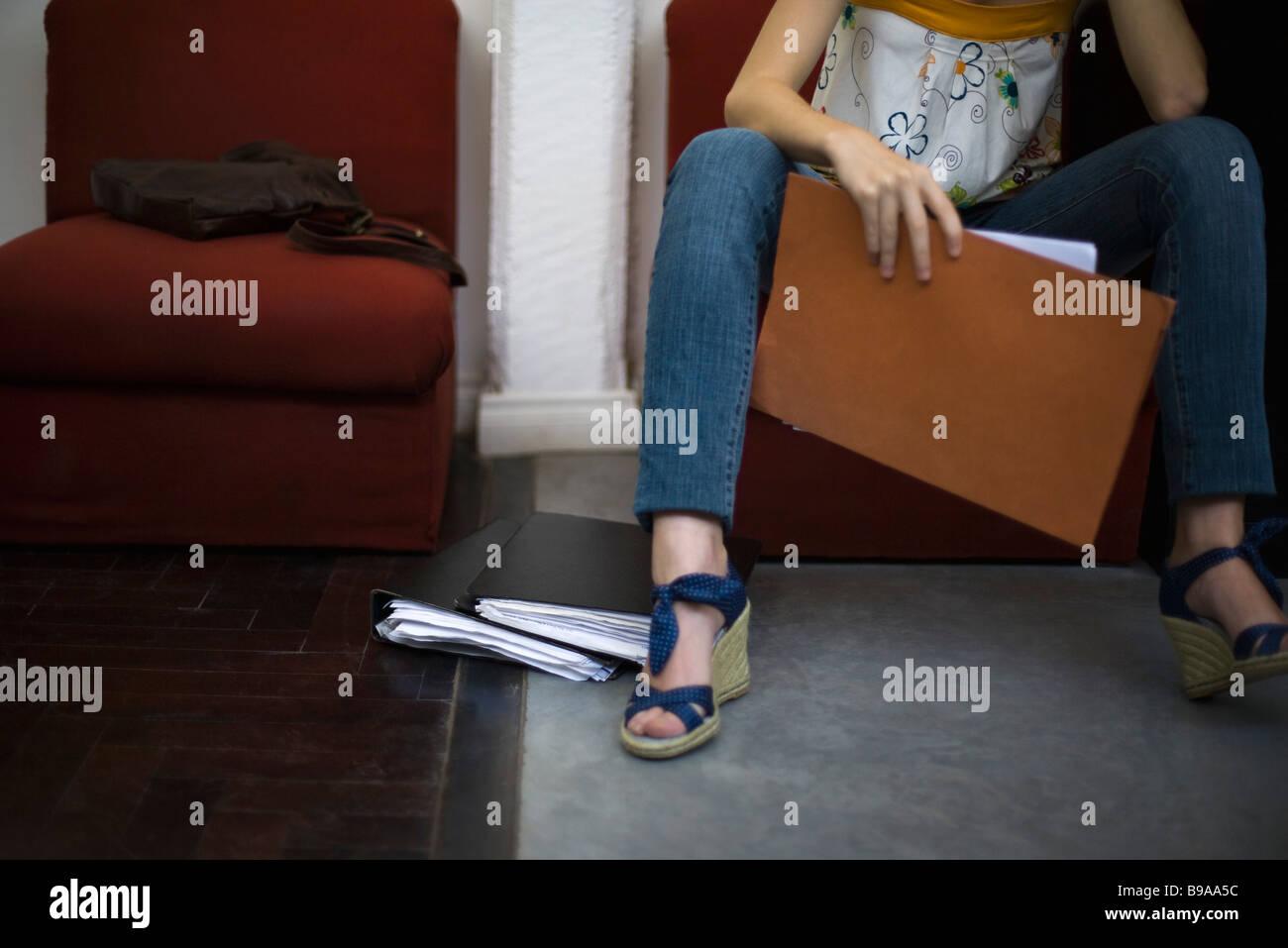 Mujer sosteniendo archivo, sentarse con las piernas separadas, recortadas Imagen De Stock