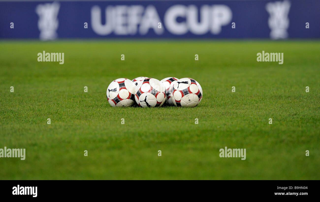 Pelotas de futbol en un campo de fútbol, delante de la publicidad perimetral con el logotipo de la Copa de la UEFA Foto de stock