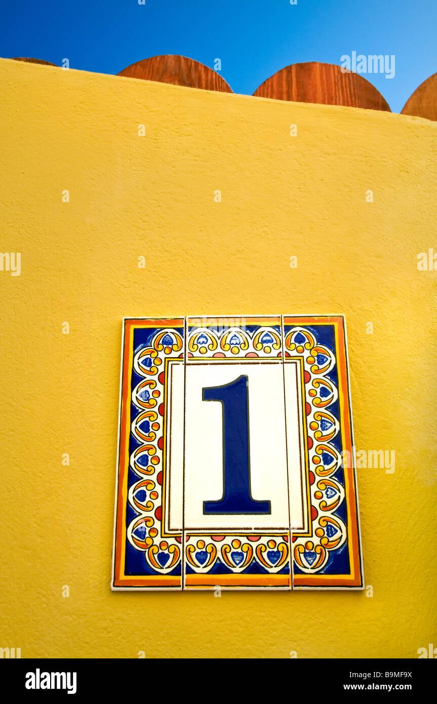 Azulejos decorativos de cerámica 'Número 1' en la pared amarilla fuera sunny holiday resort de Imagen De Stock