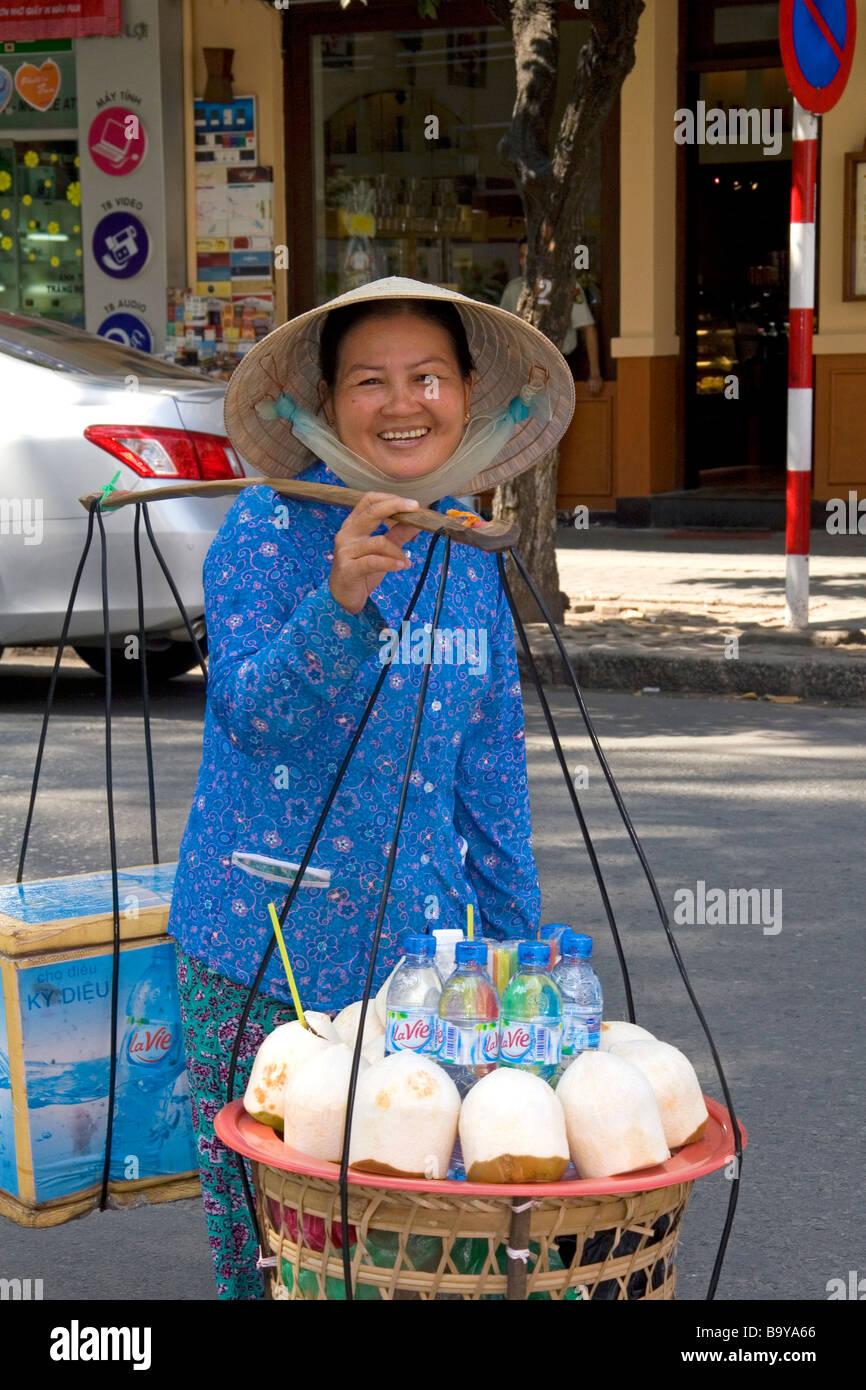 Mujer Vietnamita vendiendo cocos y agua embotellada en la calle en la ciudad de Ho Chi Minh, Vietnam Imagen De Stock