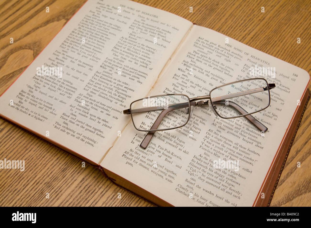 Un par de gafas de lectura apoyada en un libro de poemas de Longfellow. Foto de stock