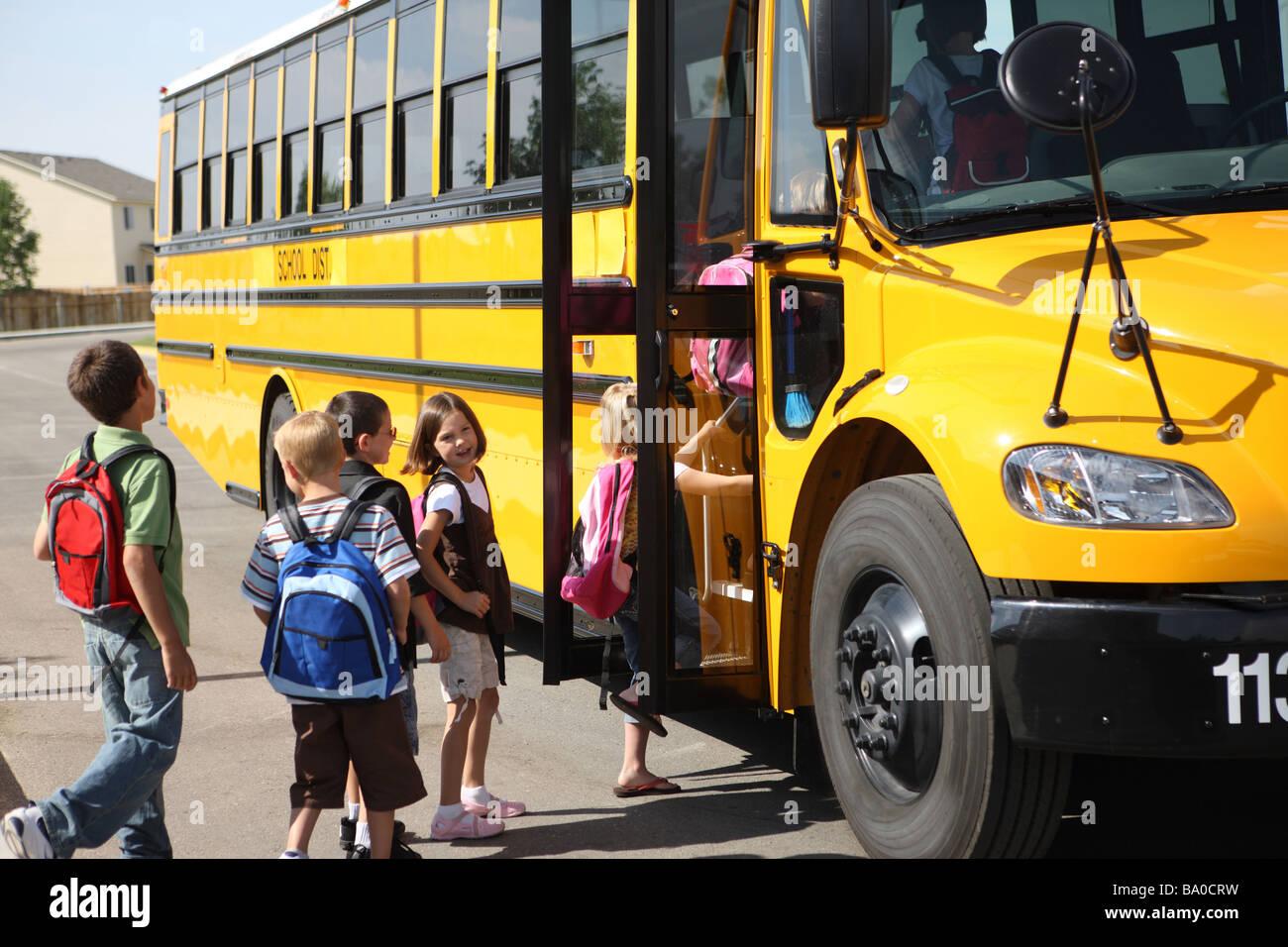 Los niños subirse al autobús escolar Imagen De Stock
