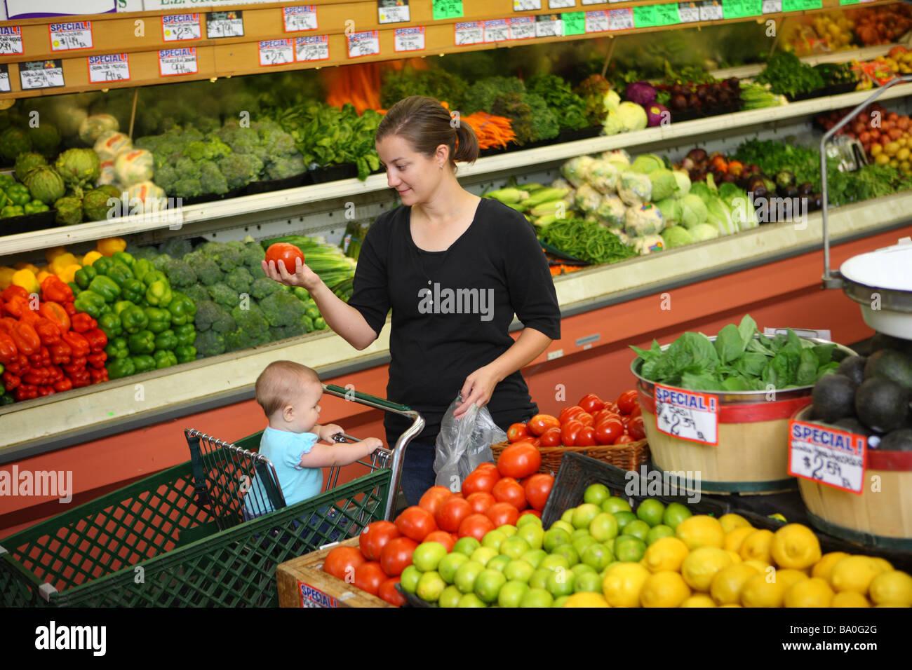 La mamá y el bebé en la tienda de ultramarinos sacando producir Imagen De Stock