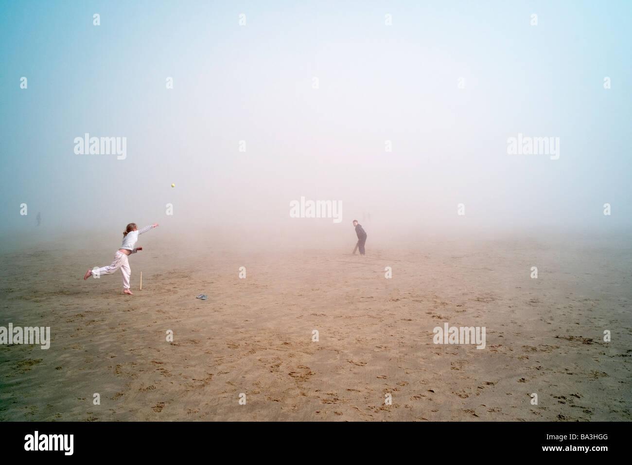 Niños jugando críquet en una niebla enlazado beach en el Sudeste de Inglaterra Imagen De Stock