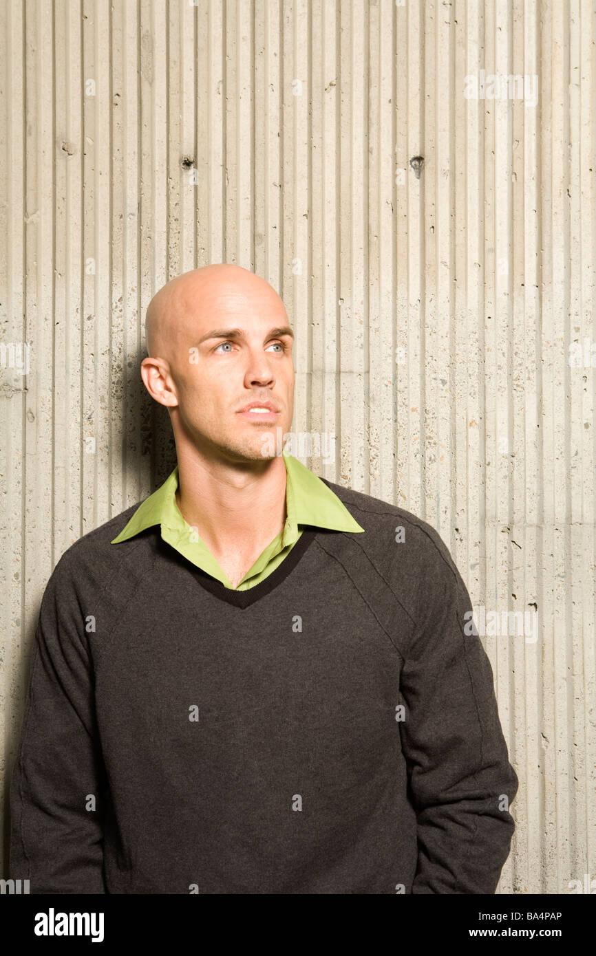 Retrato de hombre de pie junto al muro de hormigón, con una expresión definida y mirando en la distancia Foto de stock