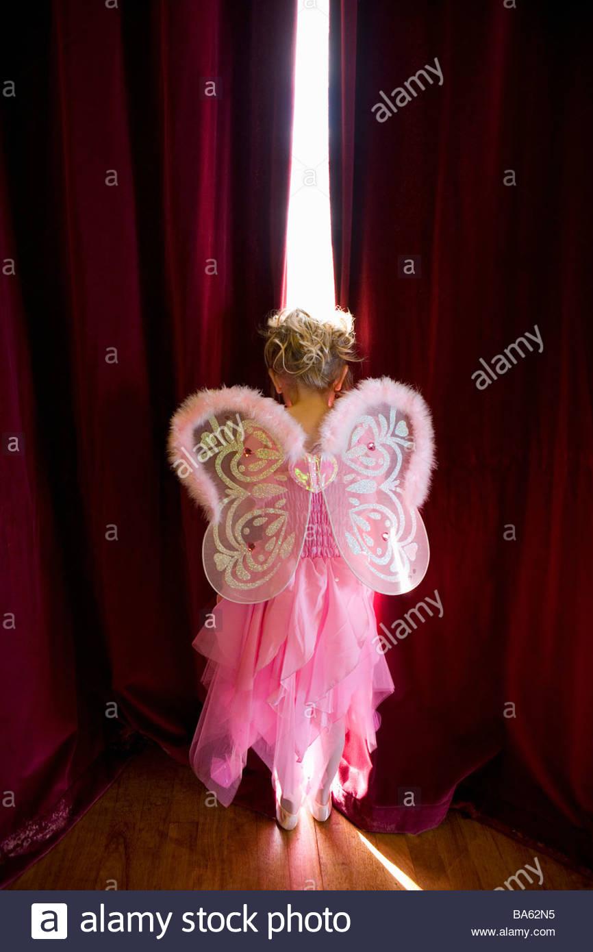 Chica (4-6) con las alas de hadas mirando brecha en cortinas, vista trasera Imagen De Stock