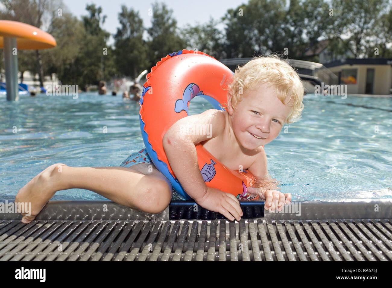 eae17ccd5 Parir neumáticos de natación piscina de borde de cuenca fuera sube gente niño  niño 3-5 años rubia sonríe feliz infancia
