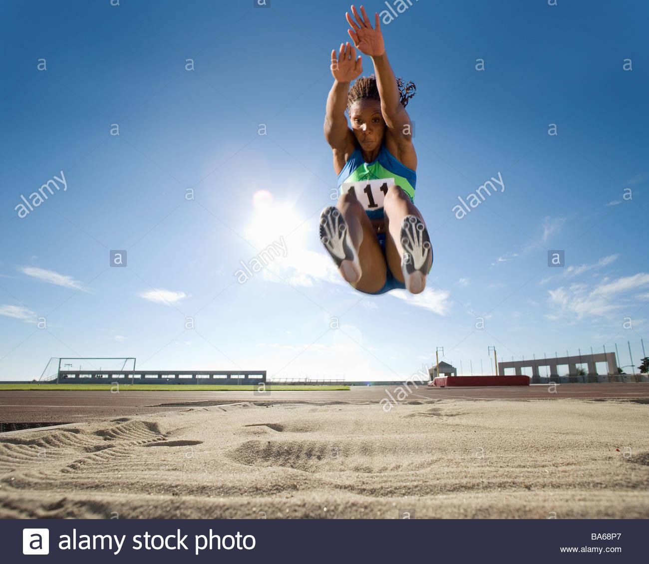 La atleta femenina africana en mitad del aire durante el salto en largo Imagen De Stock