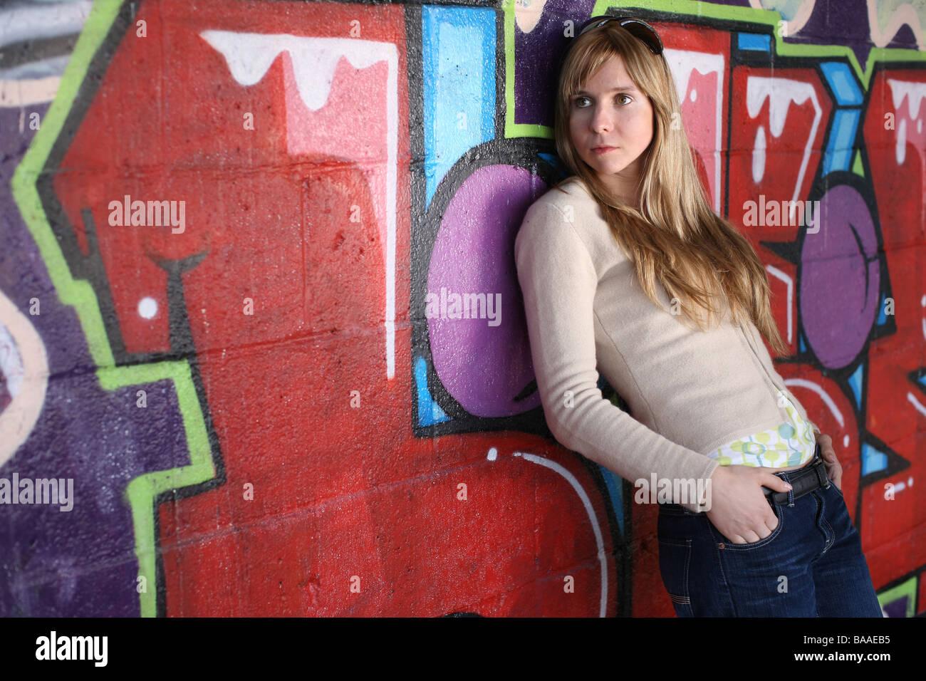 Tres cuartas partes de la longitud de la niña por graffiti wall Imagen De Stock