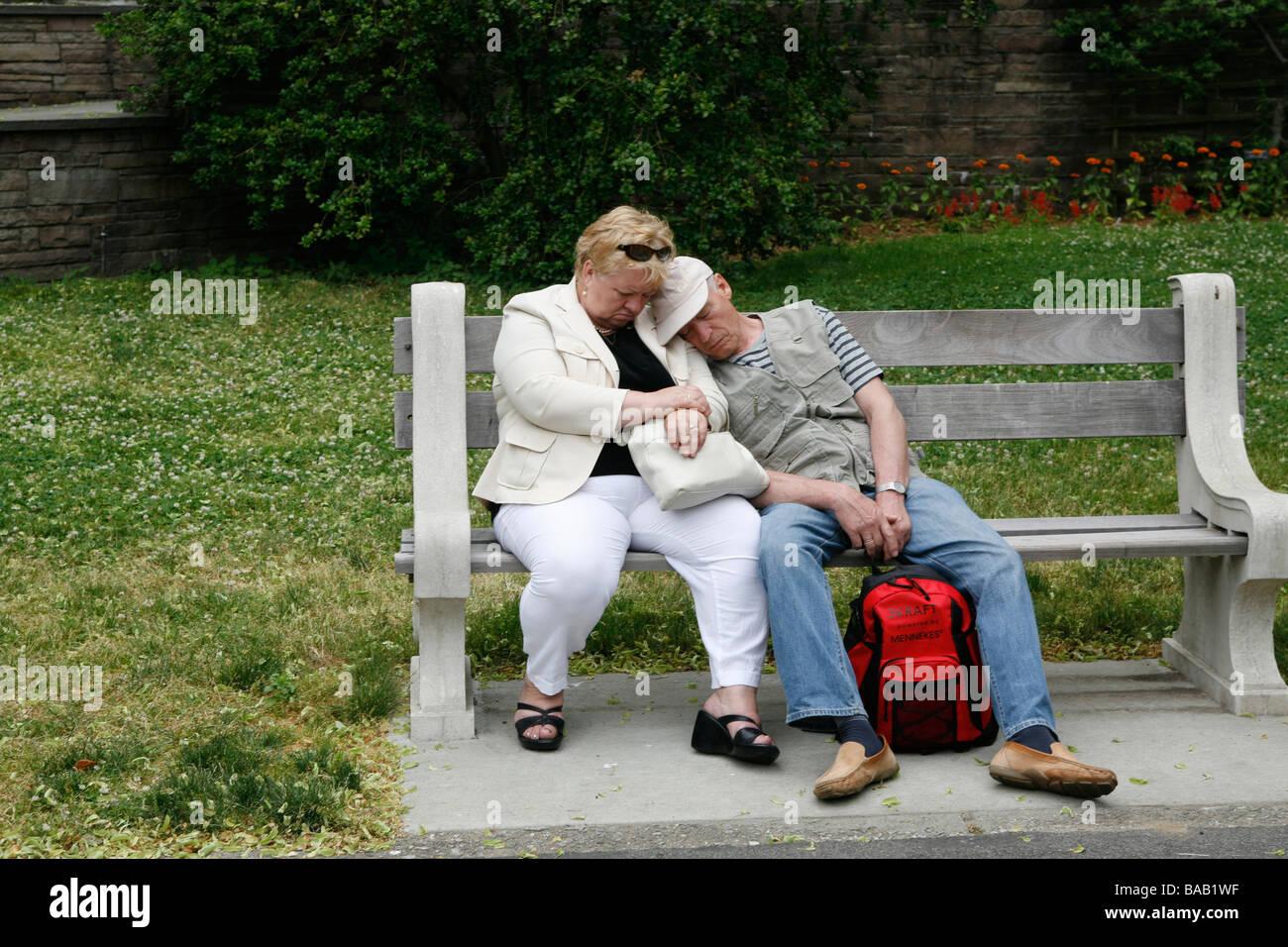 Pareja de ancianos tomar una siesta de gato en un banco en el Brooklyn Botanic Gardens en Brooklyn NY Imagen De Stock