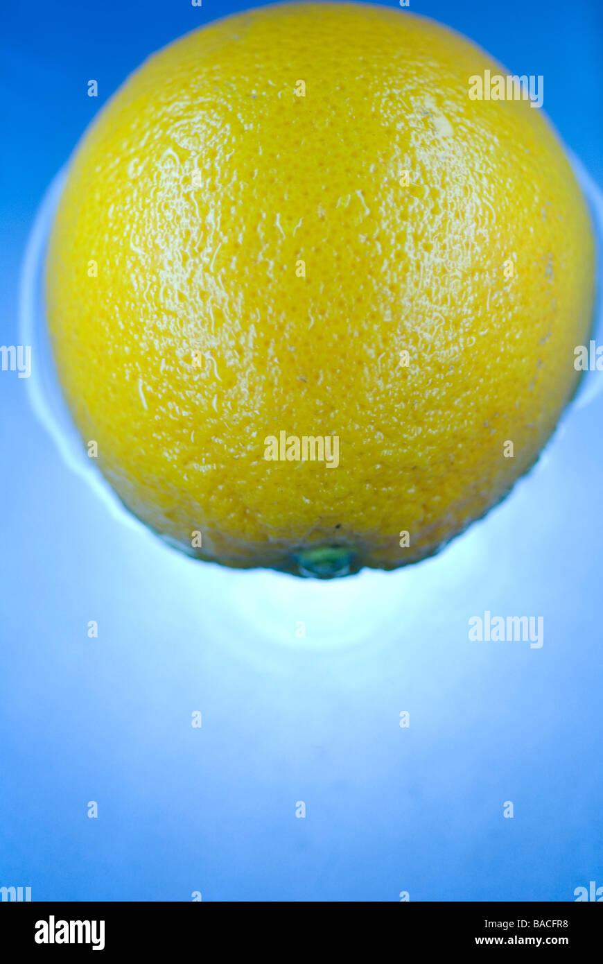 Limón flotando en el agua azul, fondo de cerca Imagen De Stock