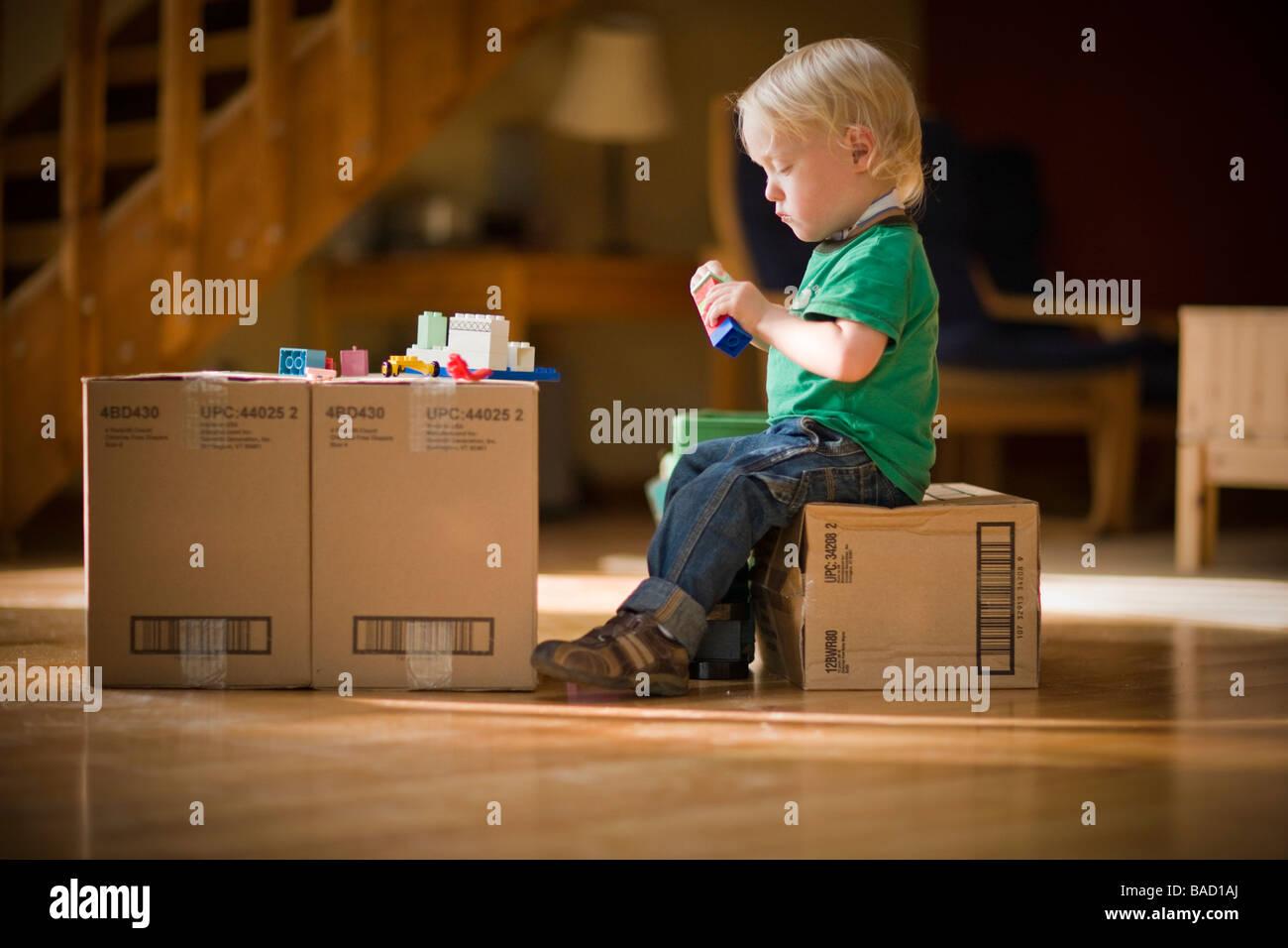 Niño jugando con juguetes en cajas de cartón Foto de stock