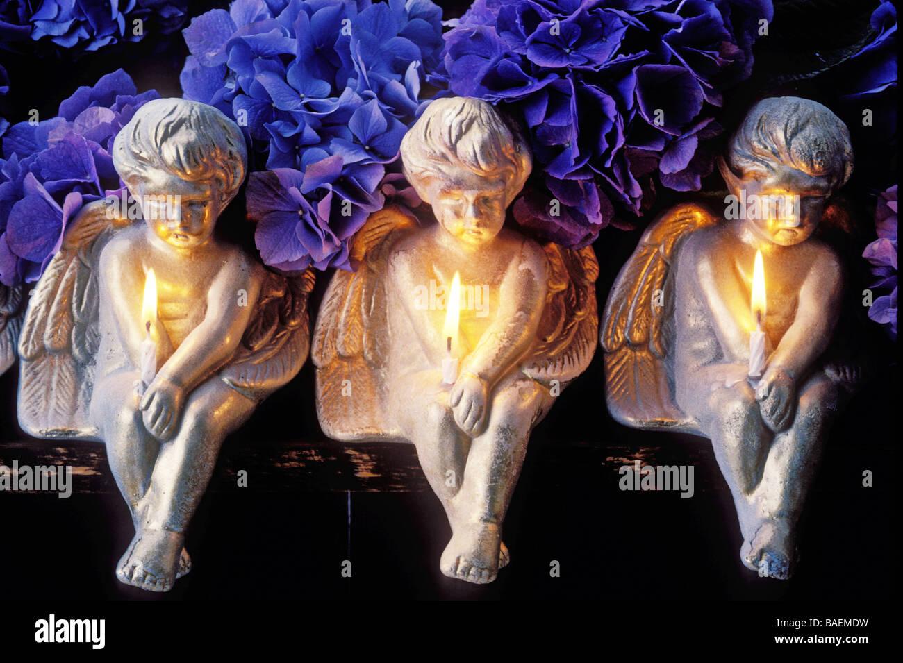 Tres ángeles sosteniendo velas Imagen De Stock