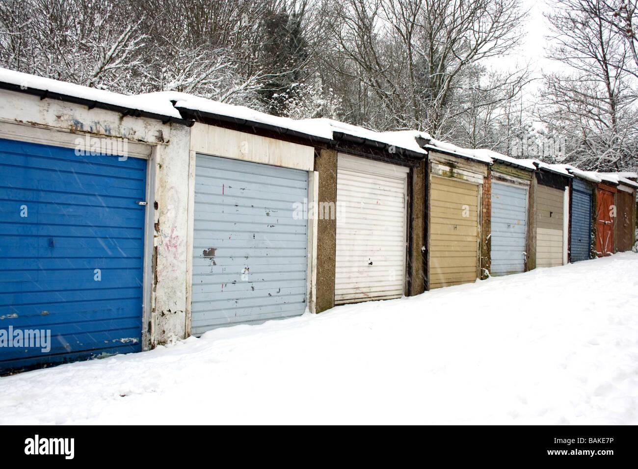 Una fila de Londres garajes con puertas de colores brillantes en contraste con la nieve y siluetas de árboles detrás Foto de stock